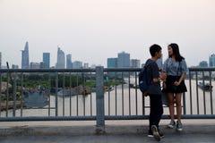 Pares asiáticos na ponte com skyline de Ho Chi Minh City no fundo fotografia de stock royalty free
