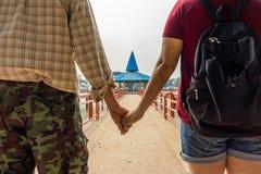 Pares asiáticos novos bonitos que guardam as mãos que olham ao pavilhão Fotos de Stock Royalty Free