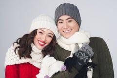 Pares asiáticos novos de sorriso que vestem o lenço morno feito malha, sobre o cinza fotografia de stock royalty free