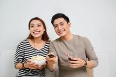 Pares asiáticos novos entusiasmado que olham a tevê e que comem a pipoca imagens de stock royalty free