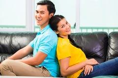 Pares asiáticos novos no sofá ou no sofá fotos de stock royalty free