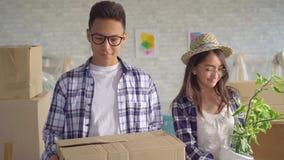 Pares asiáticos novos positivos com as caixas em suas mãos movidas em um apartamento novo video estoque