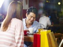 Pares asiáticos novos que conversam na cafetaria imagens de stock