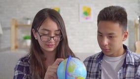 Pares asiáticos positivos jovenes con un globo en sus manos que planean un viaje almacen de metraje de vídeo