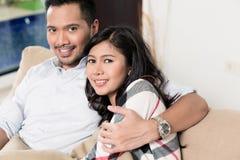 Pares asiáticos que abrazan en el sofá en sala de estar Imagen de archivo