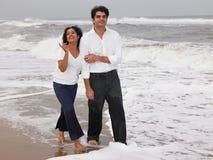 Pares asiáticos que andam na praia Foto de Stock