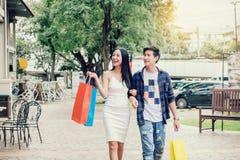 Pares asiáticos que apreciam a forma romance dos sacos de compras da despesa dentro imagens de stock