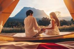 Pares asiáticos que apreciam o acampamento exterior olhando o por do sol na natureza fotos de stock royalty free