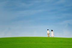 Pares asiáticos que caminan en la colina verde Imagenes de archivo