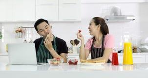Pares asiáticos que comen el pan y la fresa junto metrajes
