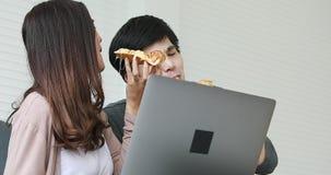 Pares asiáticos que comen la pizza junta, ella metrajes
