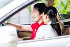 Pares asiáticos que conducen el nuevo coche Imágenes de archivo libres de regalías