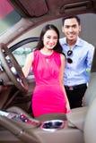 Pares asiáticos que escolhem o carro luxuoso no negócio Imagem de Stock Royalty Free