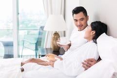 Pares asiáticos que gandulean en cama en la mañana Fotos de archivo libres de regalías