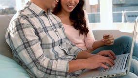 Pares asiáticos que hacen compras en línea usando el ordenador portátil y la tarjeta de crédito libre illustration