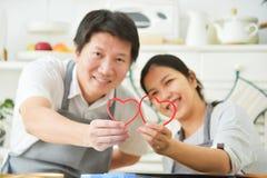 Pares asiáticos que llevan a cabo corazones rojos Fotos de archivo
