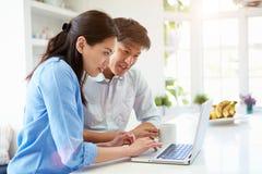 Pares asiáticos que olham o portátil na cozinha Imagem de Stock