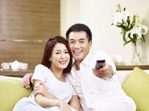 Pares asiáticos que olham a tevê em casa imagem de stock royalty free