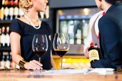 Pares asiáticos que prueban el vino rojo en barra Foto de archivo