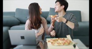 Pares asiáticos que se sientan comiendo la pizza junta almacen de metraje de vídeo