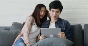 Pares asiáticos que sentam-se no sofá e na fala vídeos de arquivo