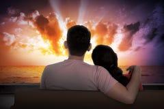 Pares asiáticos que sentam-se no sofá que olha o por do sol Imagem de Stock Royalty Free