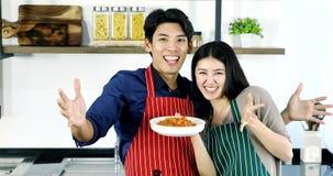 Pares asiáticos que sonríen y que muestran sus espaguetis metrajes