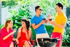 Pares asiáticos que tienen barbacoa y que beben el vino Foto de archivo libre de regalías