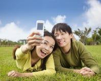 Pares asiáticos que toman la foto por el teléfono elegante Imagen de archivo libre de regalías