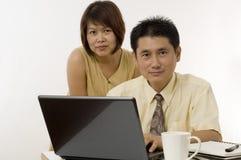 Pares asiáticos que trabajan junto Foto de archivo
