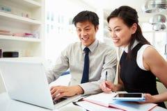 Pares asiáticos que trabalham da casa que olha finanças pessoais Foto de Stock