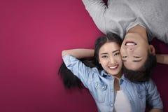 Pares asiáticos románticos que miran para arriba mientras que se acuesta Imágenes de archivo libres de regalías