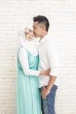 pares asiáticos románticos que se colocan con el fondo blanco de la pared Fotografía de archivo libre de regalías