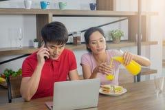 Pares asiáticos, sentando-se na mesa de jantar Os homens estão olhando o portátil e estão falando no telefone imagem de stock royalty free