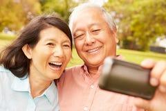 Pares asiáticos superiores que tomam Selfie no parque junto Fotografia de Stock