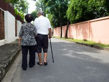 Pares asiáticos superiores românticos felizes que andam e que guardam as mãos na estrada na vila O conceito de pares superiores e fotografia de stock royalty free