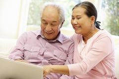 Pares asiáticos superiores usando o portátil fotografia de stock royalty free