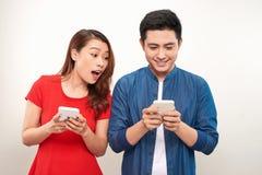 Pares asiáticos usando dispositivos: menina bonita que datilografa uma mensagem no telefone celular quando sua posição do noivo a fotos de stock