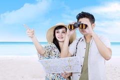 Pares asiáticos usando los prismáticos en la playa Imagenes de archivo