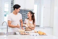 Pares asi?ticos que cozinham e que cozem o bolo junto na sala da cozinha Homem e mulher que olham entre si em casa Amor e felicid imagens de stock royalty free