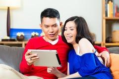 Pares asiáticos en el sofá con una PC de la tableta Imagenes de archivo