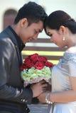 Pares asiáticos felices en el amor que sostiene la flor Imagen de archivo