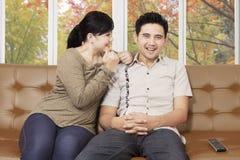 Pares asiáticos felices en un sofá en casa Imagenes de archivo