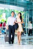 Pares asiáticos que llegan en hotel Imagen de archivo