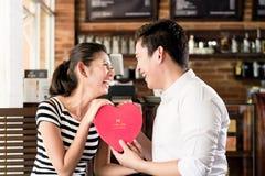 Pares asiáticos que tienen fecha en cafetería con el corazón rojo Fotos de archivo