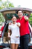Pares asiáticos que viajan con el nuevo coche Fotos de archivo libres de regalías