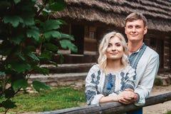 Pares asombrosos de la boda que llevan a cabo las manos y que abrazan contra un fondo de una casa de madera fotos de archivo libres de regalías