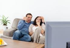 Pares asustados que miran una película de terror en la TV Imagenes de archivo