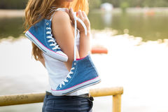Pares atados de zapatillas de deporte que cuelgan en una muchacha Imagen de archivo libre de regalías