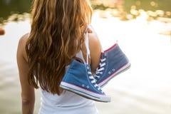 Pares atados de zapatillas de deporte que cuelgan en una muchacha Fotos de archivo libres de regalías